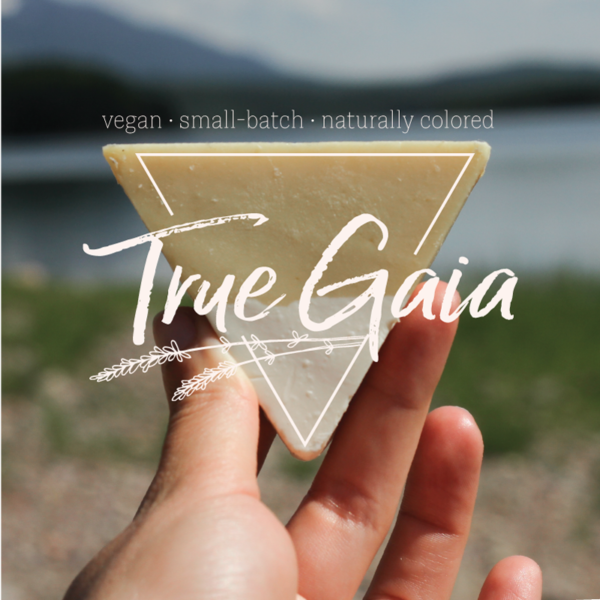 "A hand holds a triangle of soap in front of a background of water and mountains. The True Gaia logo is over top of the triangle soap, the tagline reads ""Vegan. Small-batch. Naturally colored."""