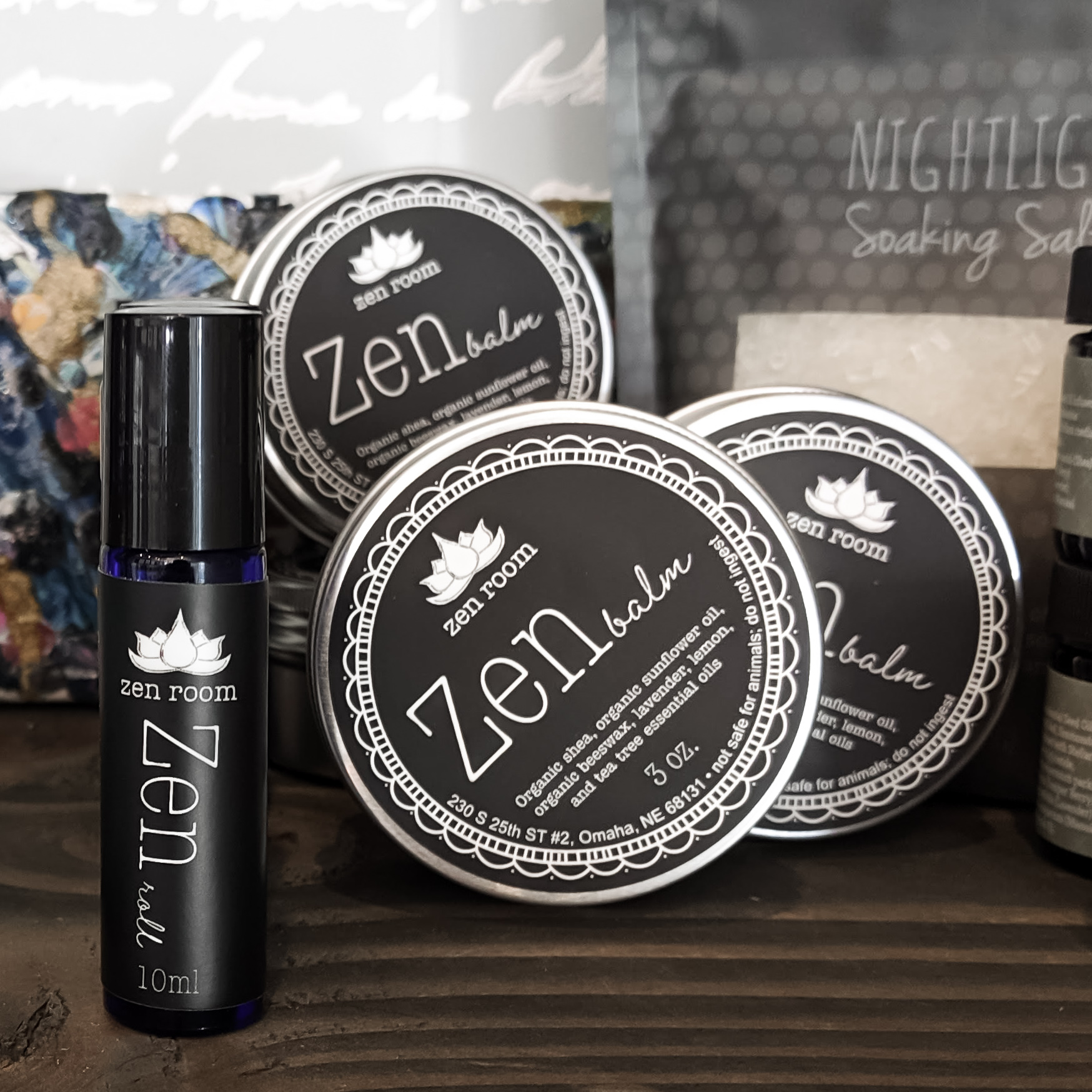 Black labels on a glass cylinder and metal tin, reading Zen roll and Zen Balm.
